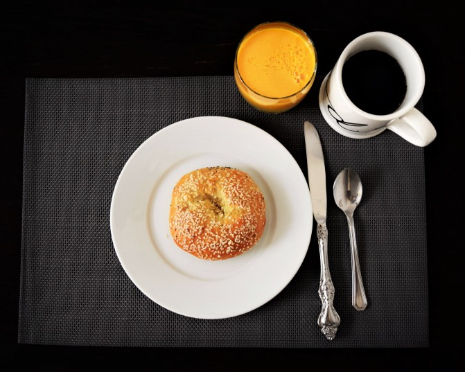 breakfast image with bagel coffee and a cup of orange juice